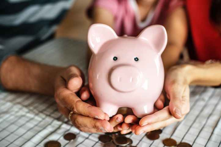 person holding pink piggy coin bank 52 week savings challenge