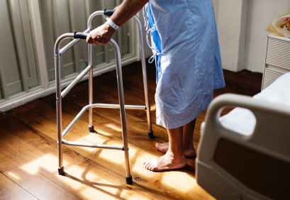 person in hospital gown using walking frame beside hospital bed walker back surgery