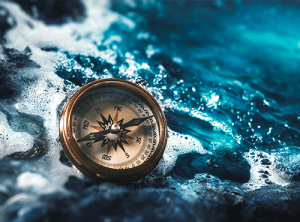 Compass on blue ocean rocks