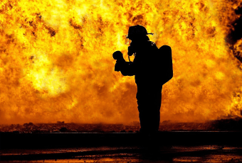 Silhouette of a firefighter in front of a blaze