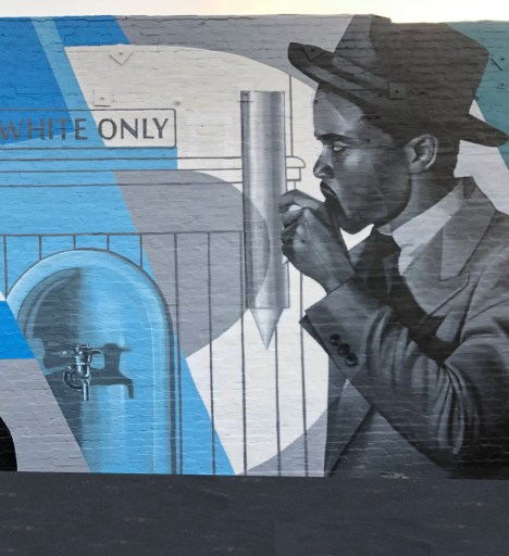 """A black and white painting of Chadwick Boseman as Thurgood Marshall drinking water against a backdrop of a """"Whites Only"""" water fountain"""