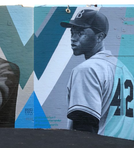 A black and white portrait of actor Chadwick Boseman as Jackie Robinson against a blue and green geometric background
