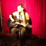 performing with guitar at Stonewall Inn