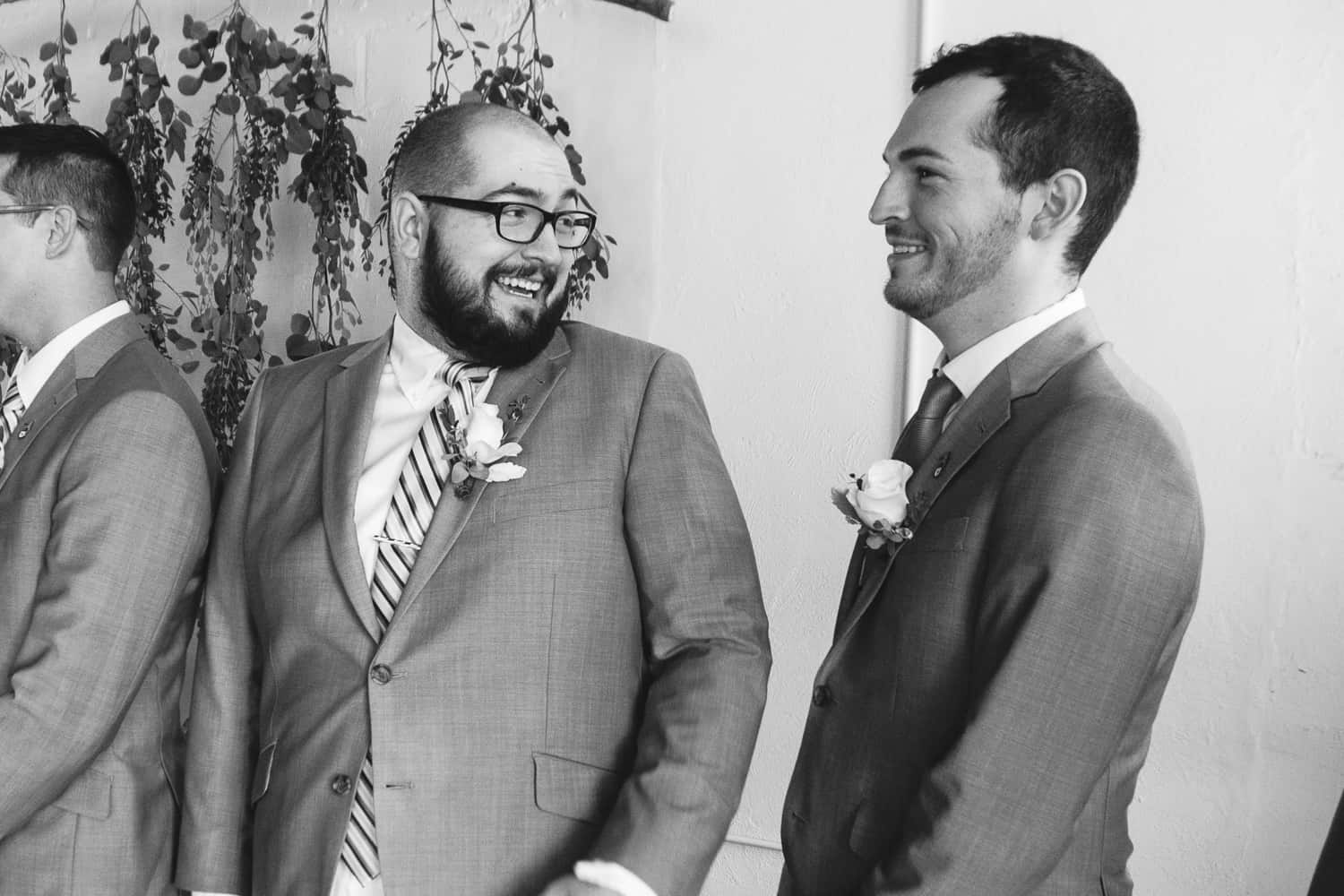 a groomsman turns to another while laughing.