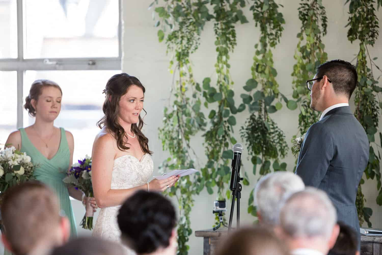 the bride and groom exchange their vows and she winks and he laughs.