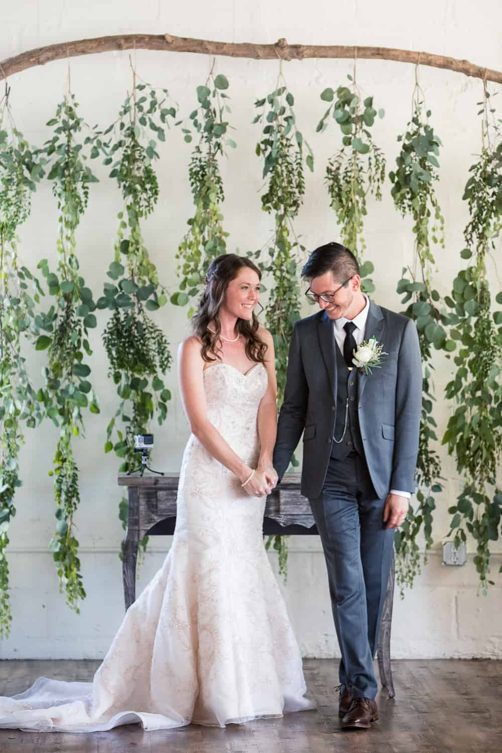as they walk down the wedding aisle, there are hanging leaves behind them. it is beautiful.