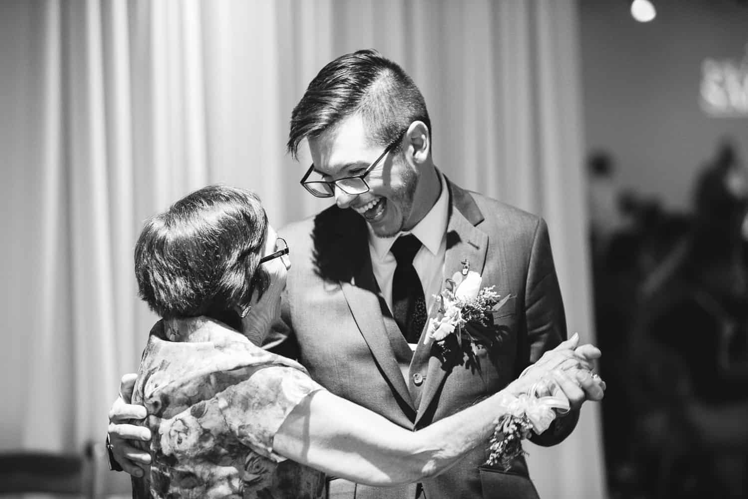 a black and white photo of the groom dancing with his grandma.