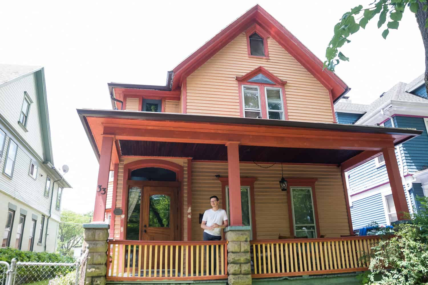 a groom standing on a porch of a house what is ornage and rust colored.