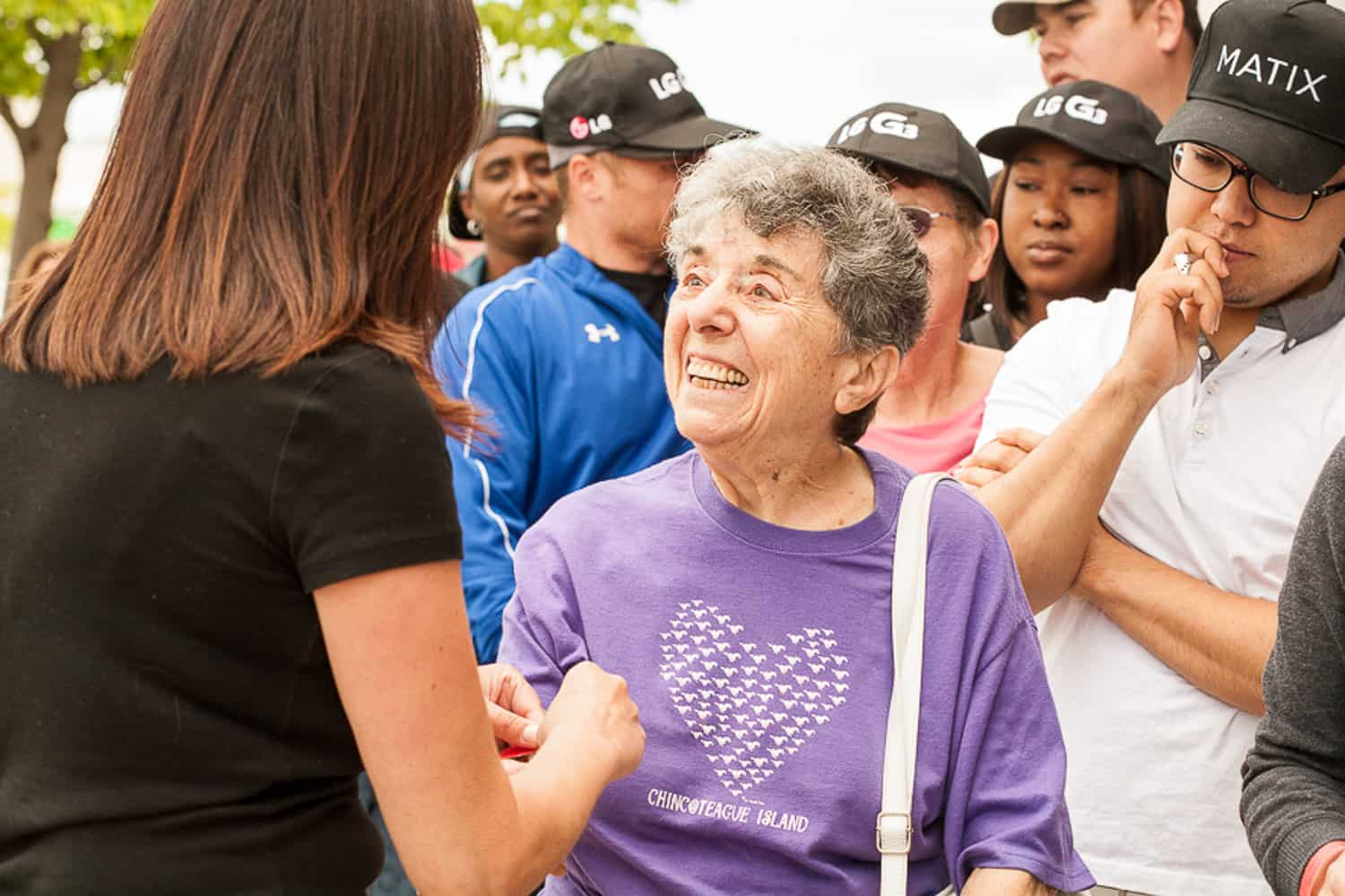 Event photograph of a staff member applying a bracelet to a person in line.