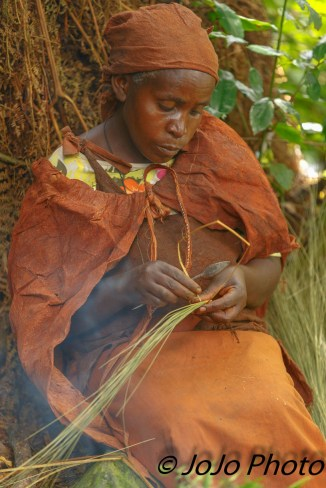 Batwa Pygmy woman weaving basket in Bwindi National Park