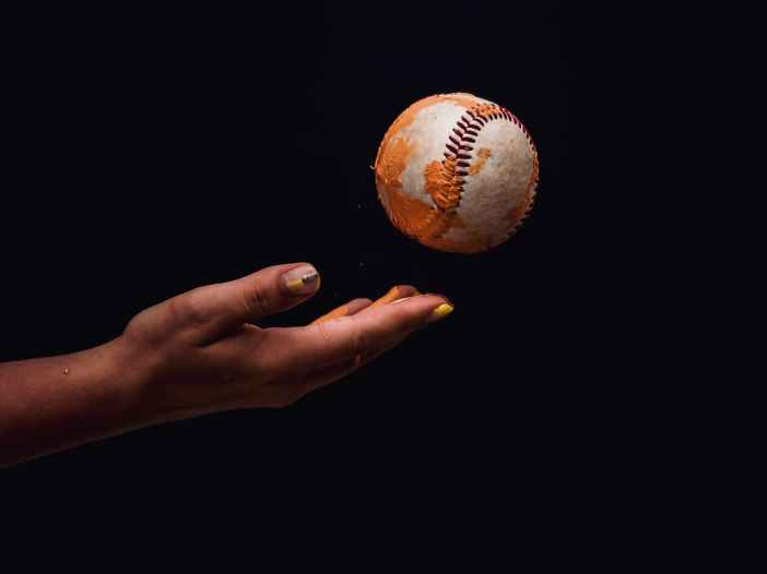 photo of person s hand throwing a baseball