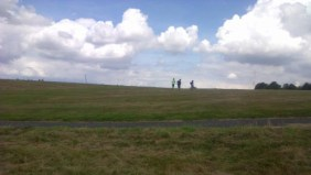 Three boys going up a hill to play football