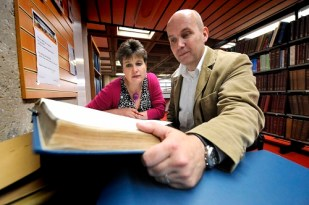 Jo Ind llooking at a big book with a family historian - for Jo Ind's blog: What is a writer?