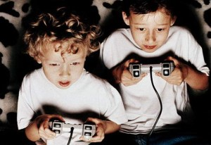 two kids playing playstation one in the dark