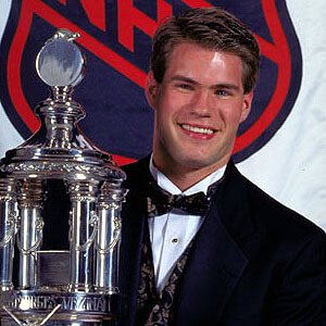 Jim Carey holds the Vezina Trophy in 1996 just as Carter Hart hopes to someday in the future