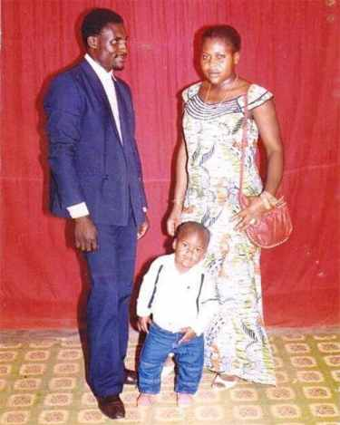 Francis Ngannou stands with his parents as a small child in Cameroon.