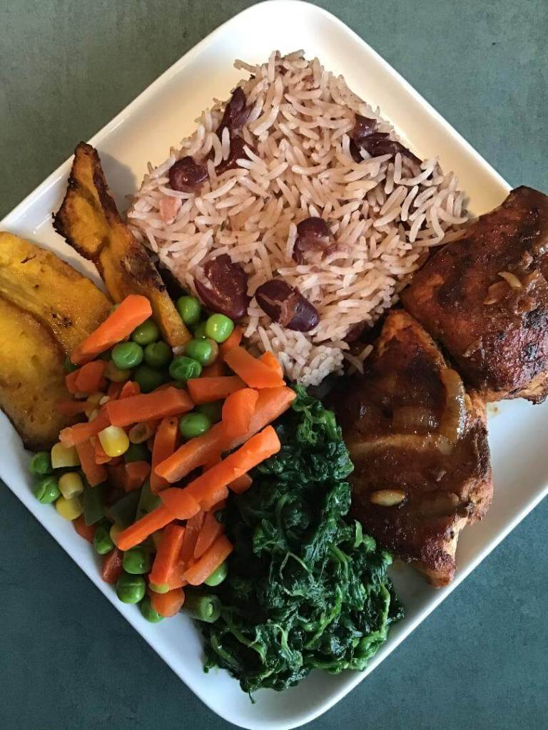 A serving dish of jamaican rice and peas, chicken, fried plantains, spinach and mixed vegetables.