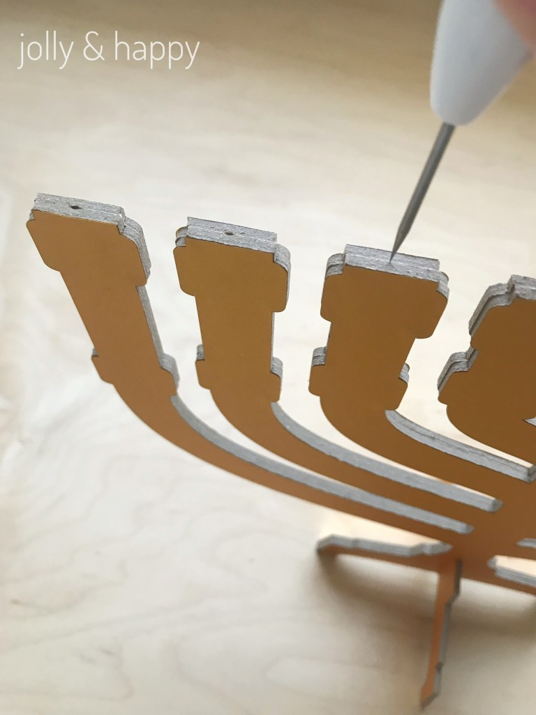 use tool to make a hole in each candle stick of the menorah