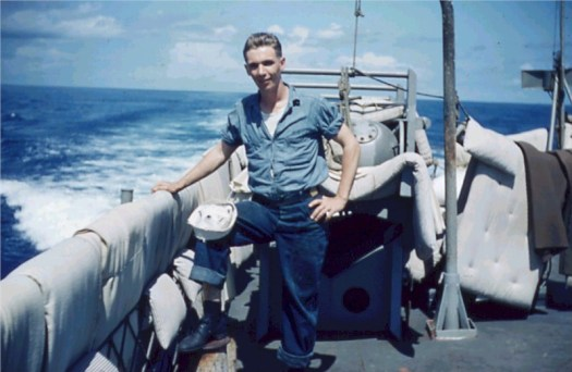 A photo of Harold Jackson on the USS Allen M. Sumner with bedding draped over the railings.
