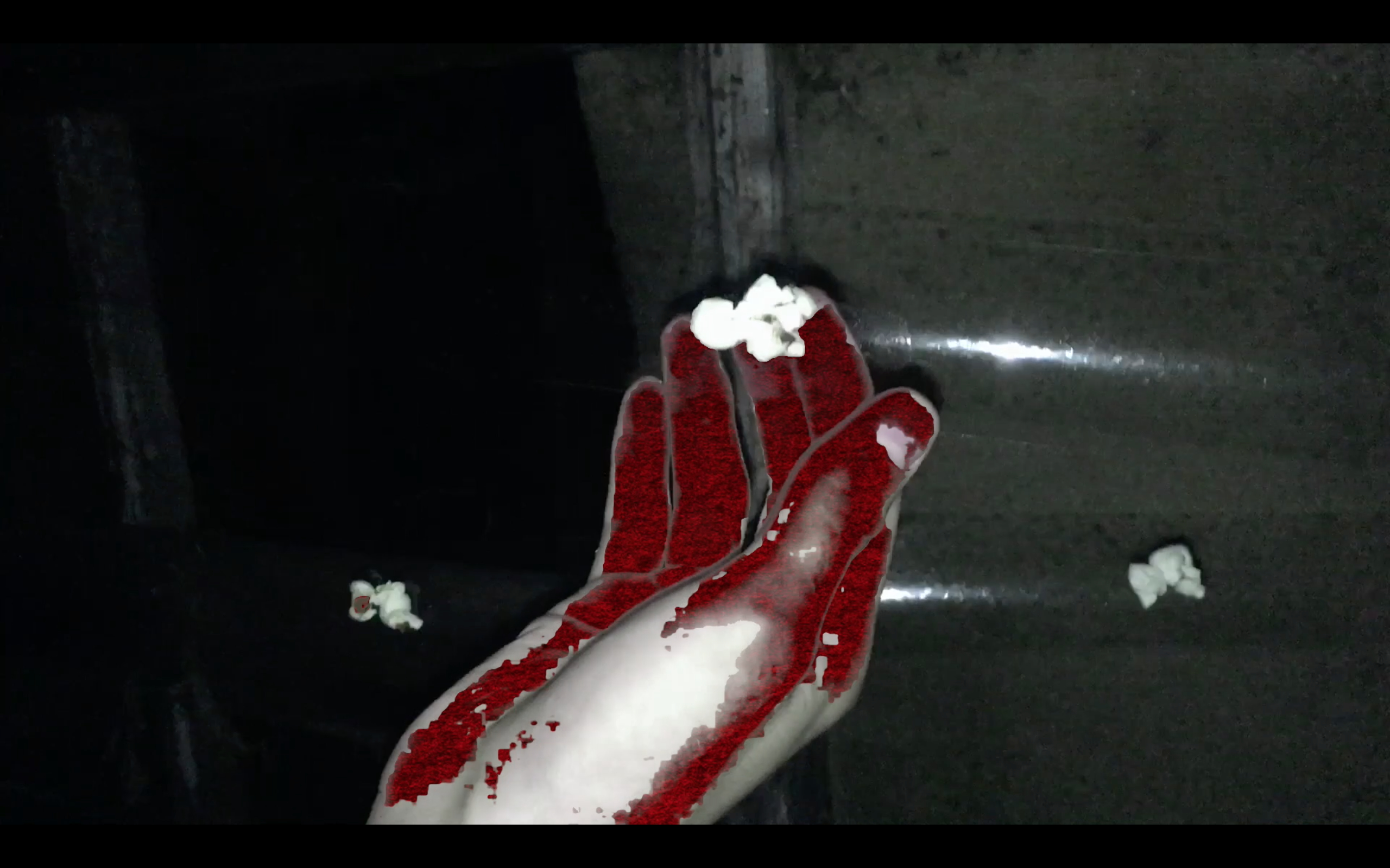 A screenshot from a video of a red hand touching a piece of popcorn stuck to some sellotape.