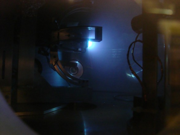 Upgraded VAT being tested in the chamber (2013). In the foreground, a Faraday Cup probe measures the ions ejected by the plasma thruster, which is firing to the right.