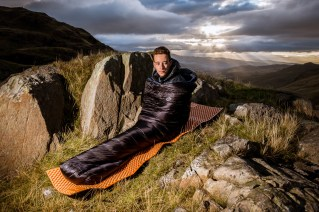 COMMERCIAL PHOTOGRAPHER - A dramatic sunrise photograph of a model in a down sleeping bag