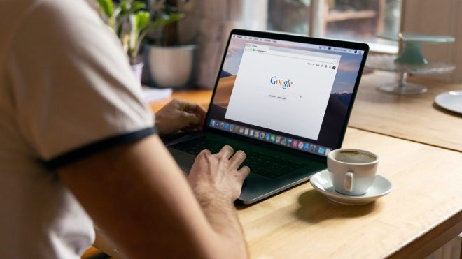 Person sitting at a table with a laptop that shows a Chrome browser on the google.com homepage.