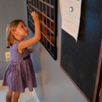 6-year-old Sophia Nelson writes on a dry-erase weekly calendar that tomorrow's her first day of school at her home in Catonsville Tuesday, Aug. 23.