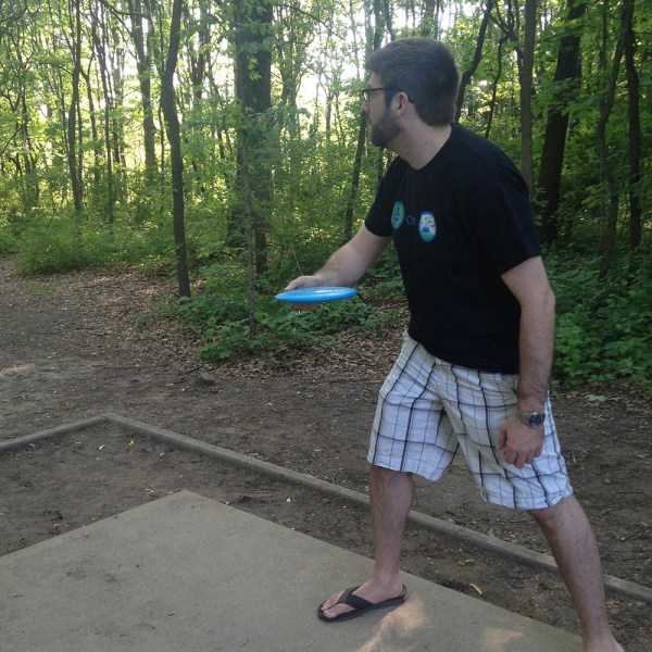 Christopher Jones throwing a disc at a disc golf tee in the woods
