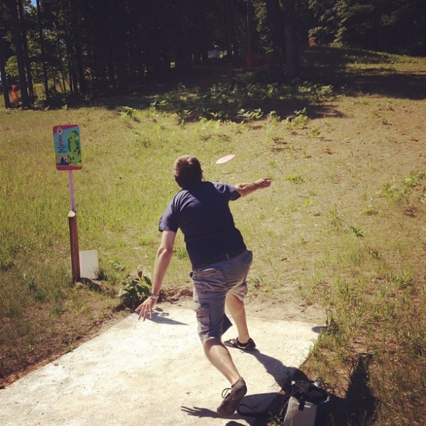 teeing off at the disc golf course