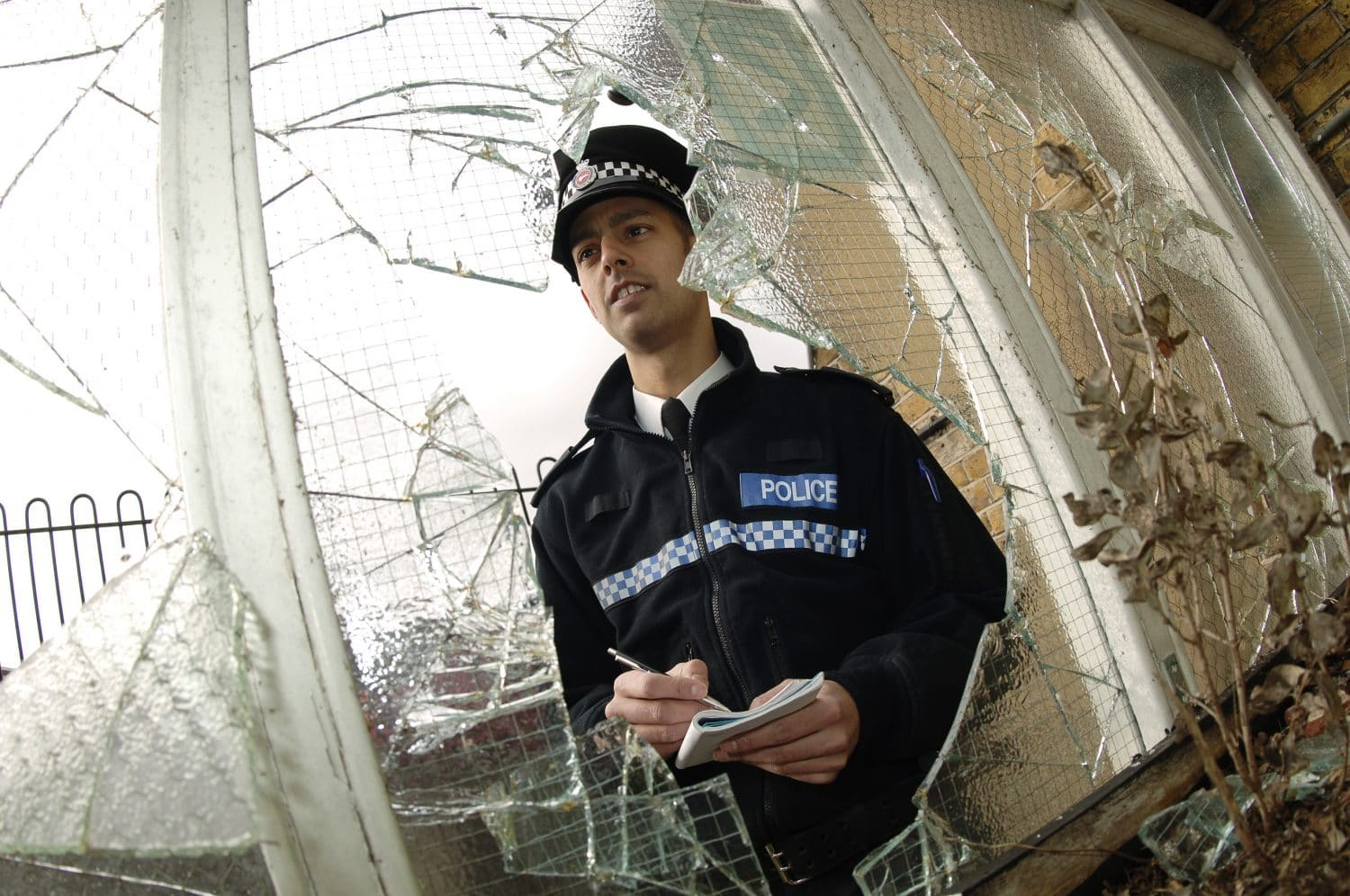 Officer looking at a broken window