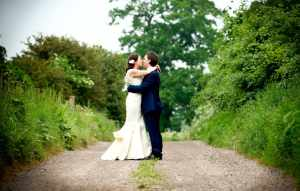Couple kissing in a quiet country lane in the Cotswolds, Tetbury
