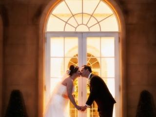 A goodnight wedding kiss outside the vine room at Northbrook Park, Farnham
