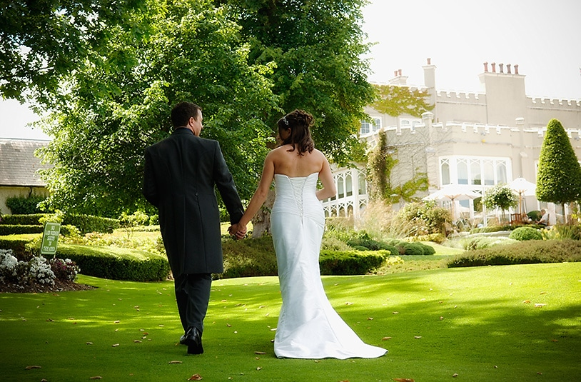 Bride and groom walking across a golf green