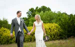 Bride and groom holding hands walking through a fiels