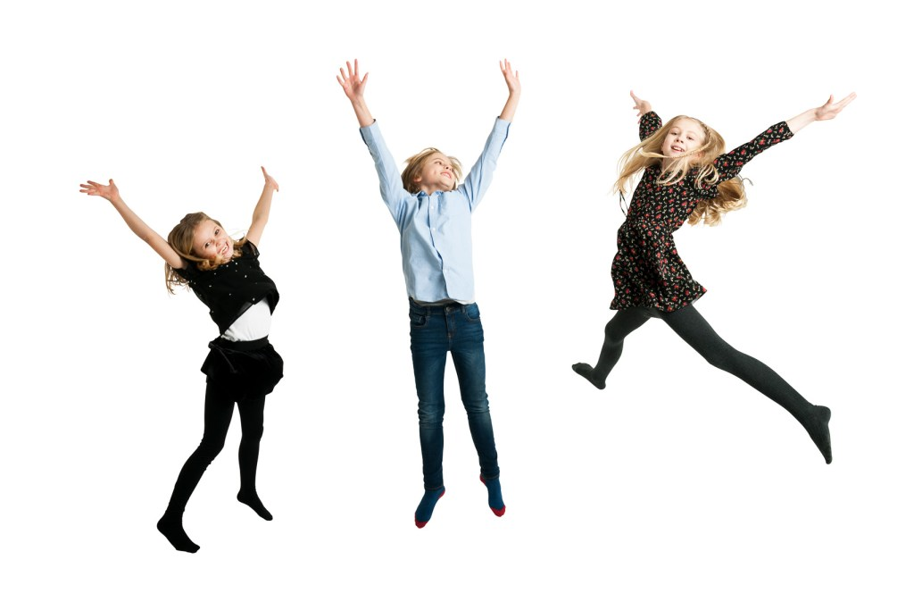3 children leaping in the air. Studio portrait against a white background.