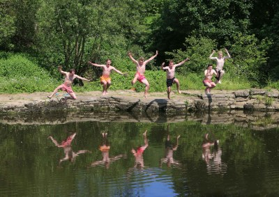Friends take a run and jump into the River Avon, near Bath.