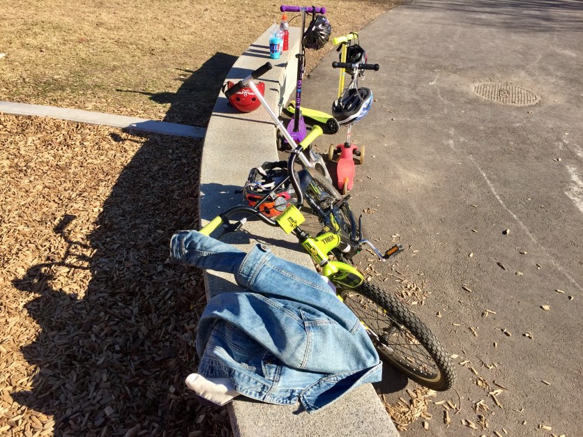 Children's bikes, helmets, and jackets lay on the sides of Pierce Park in Brookline while the playground is alive with children. Photo by Jordana Kulak