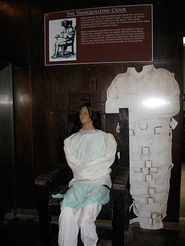 "The ""Tranquilizing Chair"" where patients were restrained until they calmed down. Beside it is a full-body straight jacket."