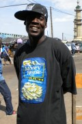 "5.- This shoe vendor's shirt says he is ""Money House Rich."""
