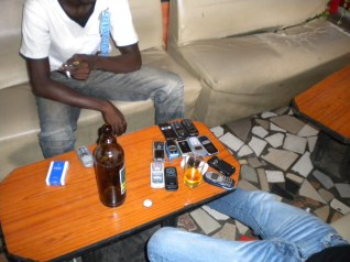"""6.- Second-hand mobile phone vendors taking a break over a """"drogba"""" beer."""
