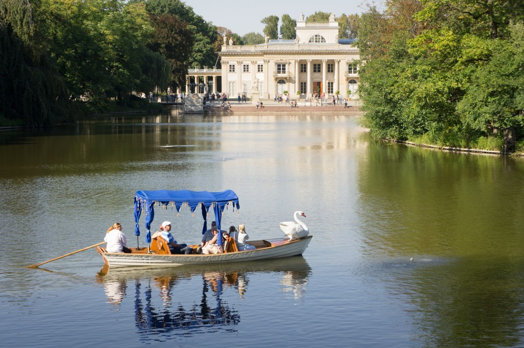 A Swan-prowed boat makes its way across the lake in front of the 'Palace On The Water'