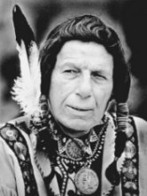A middle-aged Iron Eyes Cody, dressed in a traditional Native American cloak and with a feather on his head, in an undated publicity photo