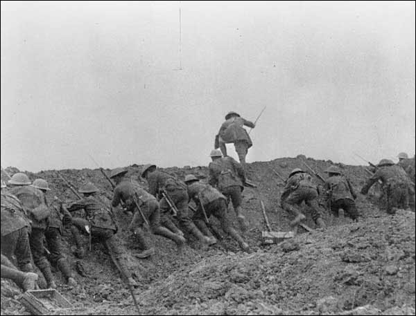 Soldiers in helmets with bayonetted rifles climb up the wall of their trench