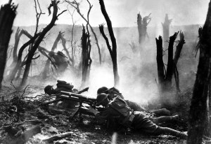 Three soldiers fire a submachine gun amidst a grove of dead trees during World War One