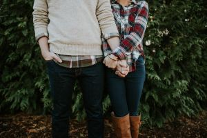 Couple in plaid holding hands and standing close near evergreen trees. Are you feeling a strain in your relationship? Considered online couples counseling in texas? Start growing closer with online couples counseling in indiana today! Contact Jordan Therapy Services via email to get started