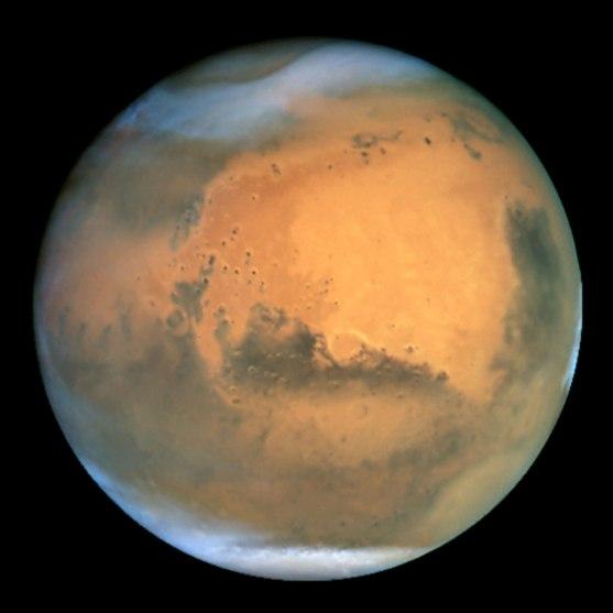 El planeta Marte visto desde el telescopio Hubble. El planeta rojo no es tan rojo; se pueden observar nubes de hielo en ambos polos y enormes tormentas de polvo en la zona inferior del polo norte, arriba a la izquierda, y en la superior del polo sur, abajo a la derecha (Imagen tomada de https://www.nasa.gov/)