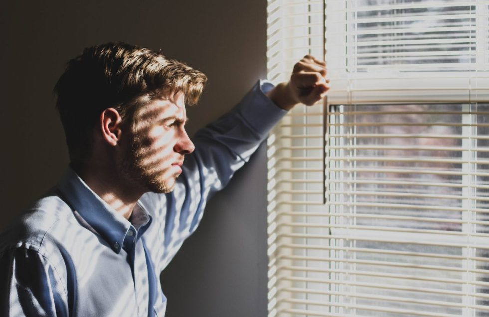 person near clear glass window pane and window blinds low-light photography