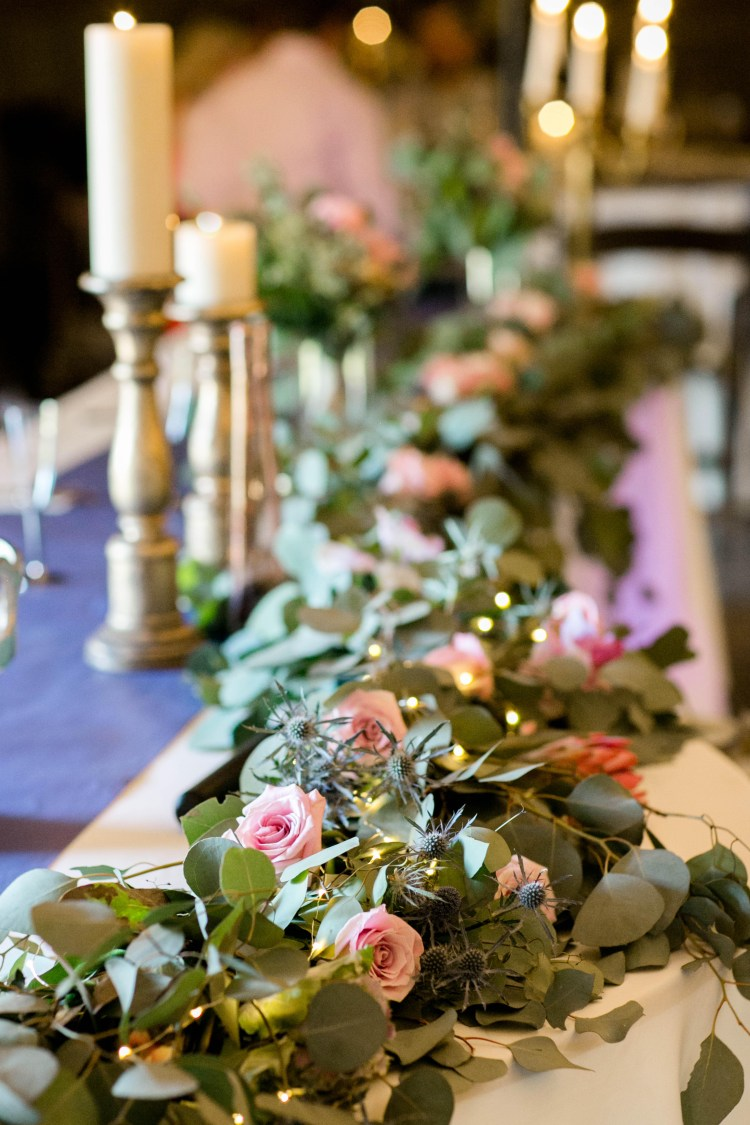 Head table garland of greenery and dusty rose accents at Cotton Creek Barn near Lubbock Texas. Flowers and planning by Jessica Ormond Events. Photography by Allee J Photography.