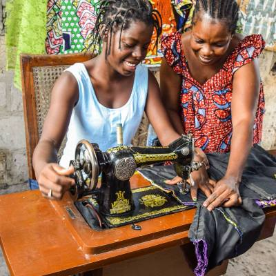 Gisele (on the right), a HOPE Congo client and tailor, teaches a young women how to sew. Photograph from Hope International.